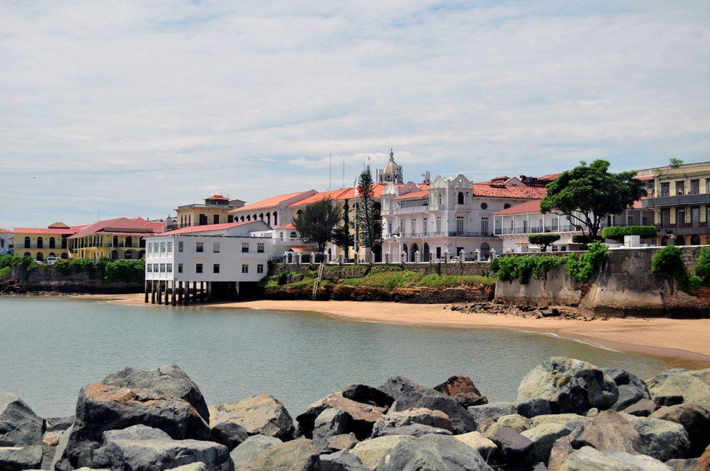 Ciudad colonial con edificios blancos frente a una playa
