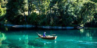 Pescador en un rio color azul cristalino en pucón
